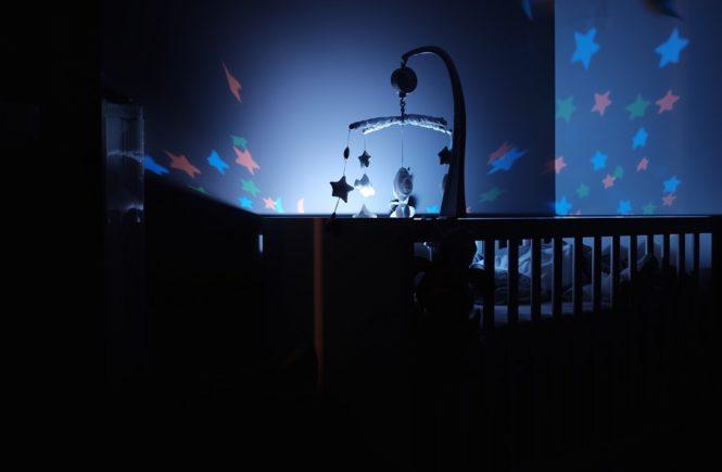 Titelbild zum Beitrag Beste Babybetten. Zu sehen ein Babybett in der Nacht mit blauer Beleuchtung
