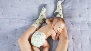 Beste Babymatratze - Baby auf Bett zwischen Mutters Beinen