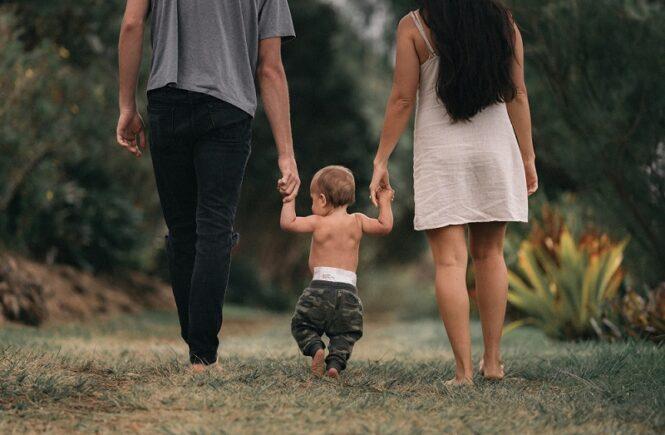 Bild zum Beitrag Reisebett Test. Zu sehen ein Baby Hand in Hand mit Mama und Papa auf einem Gehweg