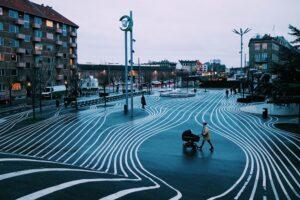 Weiteres Bild zum Beitrag Kinderwagen Test 3 in 1. Zu sehen eine Frau überquert die Strasse beim Spaziergang in der Stadt